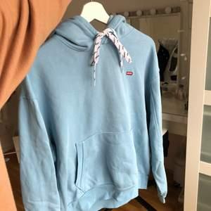Blå levis hoodie i fint skick! Storlek s men är ganska oversized. Jättefin blå färg med snygga snören❤️ köptes för ca 500-600 kr, så säljer för typ 350 då jag inte använt den så mycket men pris kan alltid diskuteras❤️ frakt ingår inte, den ligger på 66kr och då skickas det spårbart med postnord!