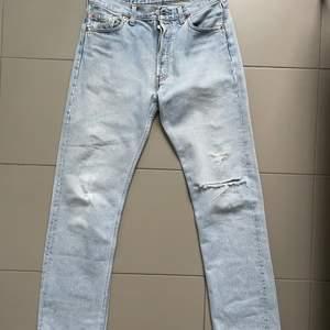 Ett par ljusa slitna Levis 501 jeans som är köpta på beyond retro i Göteborg.