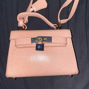 Jätte unik väska med lås och justerbara band, krokodil läder och guldiga detaljer 🤩🤩🤩 väskan är inte så stor men man får plats med lagom mycket saker i , så den är perfekt inför fester och sommaren!! (Jättebra material)
