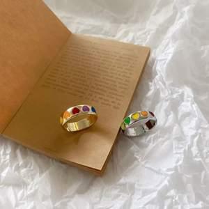 """Superfina och trendiga """"love rings"""" med färgglada hjärtan på, gjorda utav rostfritt stål. reglerbar så passar alla. Finns endast en i silver och en i guld, dvs 2 styckna ringar! Först till kvarn. 💙💚💛🧡💜❤️  priset är inklusive frakt<3"""