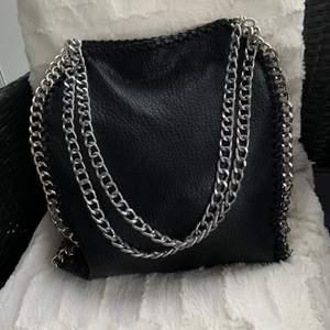 Supersnygg svart väska i skinnliknande material med silver kedja. Den är rymlig (dator och böcker får plats). Liknande Stella McCartney väska🖤 Hör av er vid frågor eller fler bilder