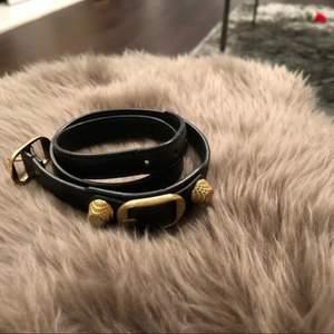 Ett svart armband med guldiga detaljer från balenciaga