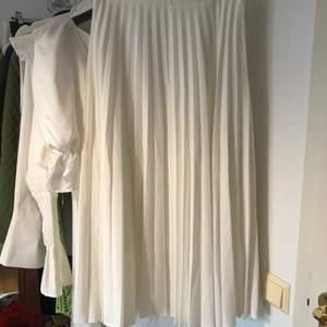 Plisserad lång/midi kjol (beror på hur lång du är) i vitt från Stradivarius. Defekter: i fram finns ett ca 1 cm långt svart streck (se andra bilden). Strl. EUR S. Frakt för detta plagg är:  45 kr. OBS! accepterar bara betalningar genom swish.