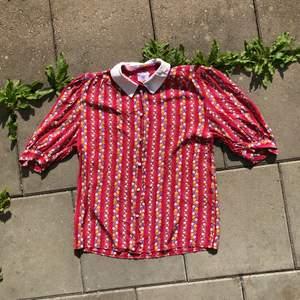 Supersöt röd skjorta med blommor och prickar. Köpt i gruppen men har endast använt den en gång då jag såg dum ut i den. Mycket fint skick och skönt material!