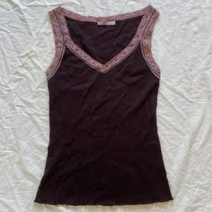 brunt ribbat linne med rosa / lila spetskanter <3 sitter bra på mig som har xs, dock ganska lös uppe i ryggen eftersom axelbanden sitter lite för brett på mig.