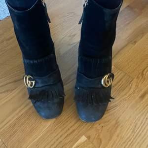 """Superfina svarta Gucci boots/klackskor. Storlek 37. Väl använda, men i fint begagnat skick. De ser smutsigare ut på bild än vad de är, svårt att fota svart mocka. Går att rengöra/putsa upp mer 💋Skokartong finns men dessvärre inget kvitto därav det låga priset. Modellen heter """"marmont suede boots"""". Guccimärket samt fransar framtill🖤"""