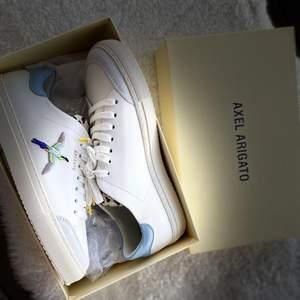 """Oanvänd sneakers """"Axel Arigato """", vit sneaker med övre läder.Prislapp på ,ingår även en väska till skorna."""