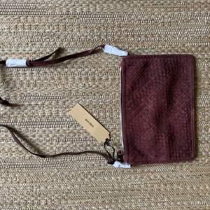Helt oanvänd väska Alana Big Suede mocka, färgen heter Bitter Chocolate. Mått: 29x20. En större version av klassiska axelremsväskan Alanya. Justerbart axelband och ett band för handleden. Ett innerrfack. Stängs med dragkedja. Nypris 1800kr.