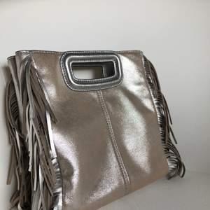 INTRESSEKOLL på min silvriga Maje väska, köpt på NK för 2799kr för ca 6 månader sen. Är i ny skick och inte använd speciellt mycket. Band finns självklart med! Vid flera intresserade blir det budgivning.