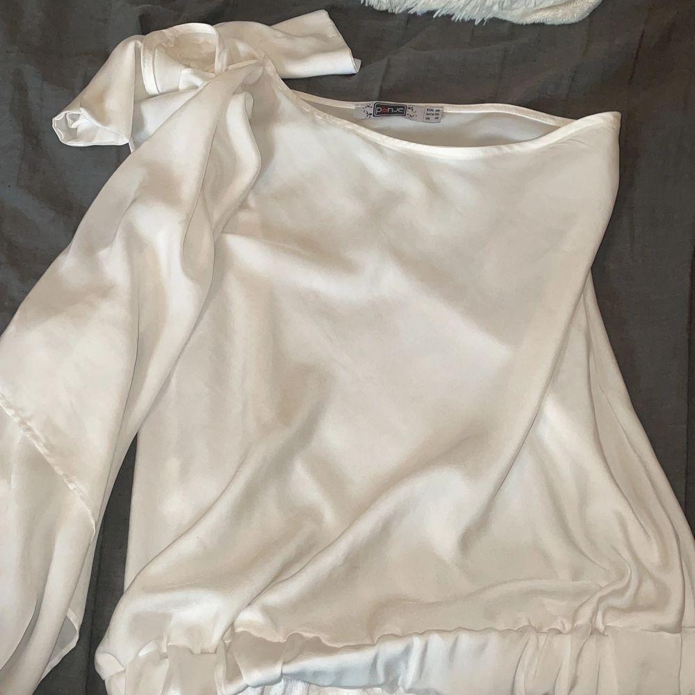 One shoulder vit tunn tröja i storlek 38z. Använd en gång, lite stor på mig. En liten fläck (syns inte när man har på sig den) därav det lägre priset! . Toppar.