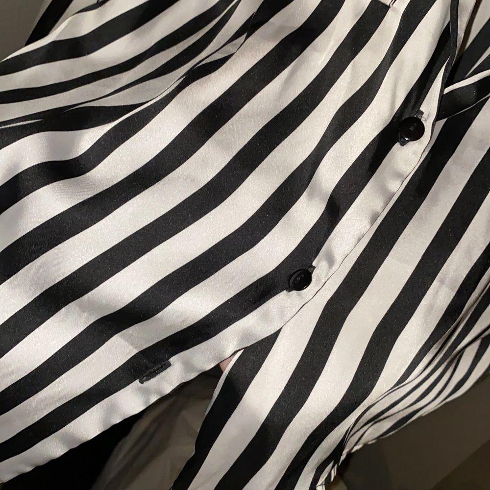 Säljer denna skjorta som är lite mer åt det kortare hållet (alltså croppad). Knappt använd men vid första tvätten försvann en knapp men med tanke på att men kan göra en rosett så märks det inte att den är borta. Den är i storlek S och passar på både XS och S beroende på hur man vill att den ska sitta. . Toppar.