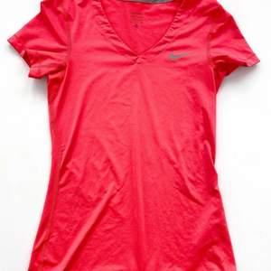 Snygg träningst-shirt från Nike i rosa/röd färg. Fin åtsittande passform. Se fler trendiga träningskläder på vår Instagram @oak_uf!