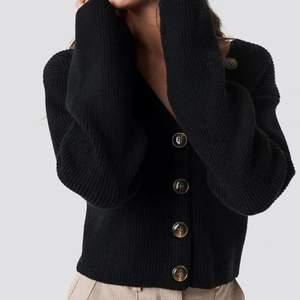 Supersöt stickad tröja från NA-KD som kan användas som både tröja men även cardigan/kofta då den går att knäppa upp helt och hållet. Croppad passform. Inga defekter.