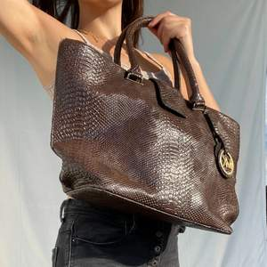 Hi, I'm selling this Michael Kors shopper in a warm brown snake skin optic. The MK sign looks pretty used (hence the price) but all in all the bag is in pretty good shape.