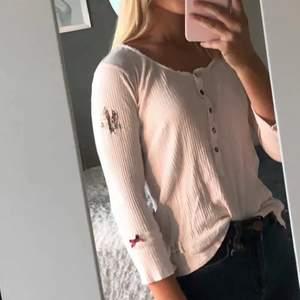 En ljus rosa tunn långärmad Odd Molly blus som har små spräckliga knappar framtill, En vinröd rosett på armen. Blusen är använd men i fint skick:)