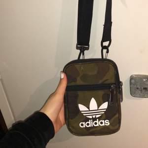 Adidas axelväska i mönster. Är lite sliten men inget som syns. Väskan är väldigt praktisk och passar på alla kön. Väldigt bra och tjockt material.