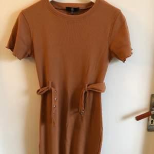 Fin kamelfärgad klänning från missguided. Aldrig använd. Strl 36. Köparen står för frakten🧡