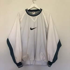 Vintage Nike sweatshirt från 90-talet. Storlek XL. Tröja har två fickor. Tröjan är i vit och blå färg. Tröjan är i använt skick men har tyvärr ett par fläckar.