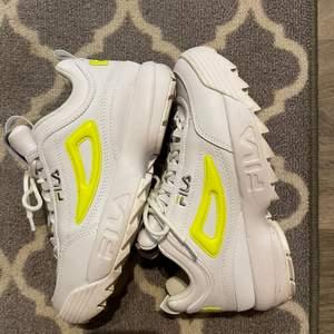 Ett par vita fila skor med neon gul logga. Knappt använda, i väldigt fint skick.