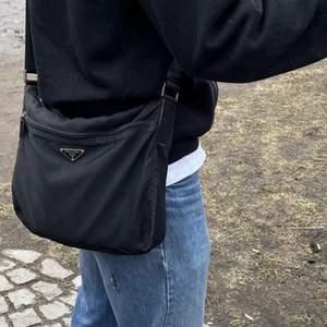 Svart Prada crossbody bag med justerbara band. Bra skick för dess ålder men några repor som syns på bilden ovan.                                                                                  Mått: bredd 29 cm höjd 23 cm