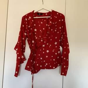 Röd blus med stjärnor på från missguided i storlek 34. plagget tvättas innan det skickas iväg