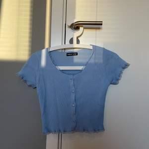 En jättefin mjuk och stretchig blå topp i storlek S. Fin blå spets längs kanten av tröjan. Går att knäppa upp och användas som en kortärmad kofta. Frakt ingår i priset!  Kontakta vid intresse.