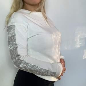 Vit tröja med glitter vid ärmarna. Är i bra skick och är i storlek 4 (motsvarar xs)☺️Om fler plaggs köps samtidigt kan pris rabatteras 💞