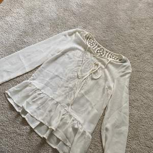 Oanvänd vit topp/blus med fint mönster på ryggen och knytning fram samt med volanger🌸 säljer för 200kr🌸💕