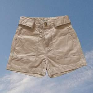 Beige shorts från Gina i fint skick. Mid-highwaist, matchande skärp. Finns inte längre att köpa. Öppen för alla frågor, kan alltid skicka fler bilder privat.