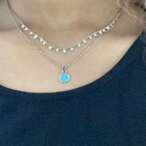 It's a golden necklace with a circle that it's blue in the middle with two layers and one of layers have white and gold beads I bought it for 200kr I I did not were that much