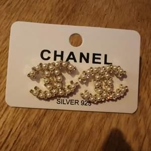 Större modell av CC inspirerade örhängen i silver. Med strass och pärlor.