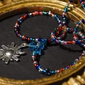 Ett pärlhalsband med massor av olika pärlor och en solberlock. Finns bara ett enda!