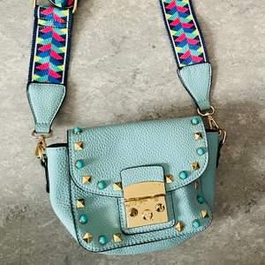 Baby blå väska (fake skinn) med guldiga och blåa nitar på. Ett färgglatt band med färgerna: marinblå, blå, hotpink, neongul och grön🌈