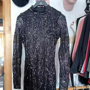 Mycket fin svart paljett klänning. Hög hals och kort. Aldrig använd!