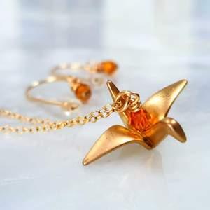 Guld färgad origami fågel halsband med tillhörande örhängen. Otroligt fint halsband med orangea glas pärlor som reflekterar ljuset så att det ser ut som att dem lyser. Kontakta vid intresse😇🐦