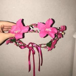 En fin blomsterkrans med rosa fakeblommor med band där bak där man justerar storlek