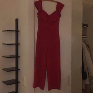 En röd jumpsuit från H&M, bra skick, ett par år gammal, bara använt en eller två gånger vid jul. Storlek S. Superfin med volanger över bysten. Köpare betalar frakt eller hämtas i Stockholm