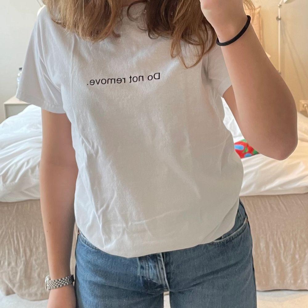 """Säljer denna asnajs T-shirt från """"Fuck art, make tees"""" med trycket """"Do not remove."""" T-shirten är i stl XS men jag som brukar ha S kan ha den så den är lite stor i storleken. Jag har använt T-shirten en eller två gånger och den är i nyskick. Materialet är inte alls genomskinligt som vita T-shirtar kan vara utan det är i bra kvalite! Säljer för 95kr + frakt!. T-shirts."""