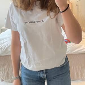 """Säljer denna asnajs T-shirt från """"Fuck art, make tees"""" med trycket """"Do not remove."""" T-shirten är i stl XS men jag som brukar ha S kan ha den så den är lite stor i storleken. Jag har använt T-shirten en eller två gånger och den är i nyskick. Materialet är inte alls genomskinligt som vita T-shirtar kan vara utan det är i bra kvalite! Säljer för 95kr + frakt!"""