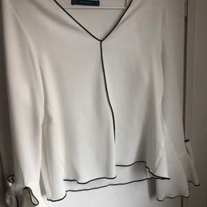 Fin vit blus med rosetter längst ner på armarna från Zara! Använd fåtal gånger, storlek S!