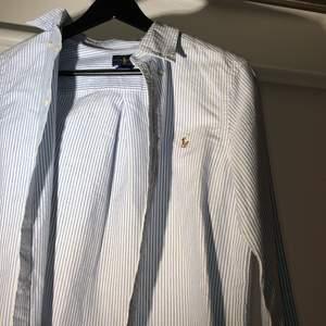Blå/vit randig skjorta från polo Ralph lauren i väldigt skönt material. Perfekt nu till sommaren. Passar perfekt om man är runt 165cm. Nypris ligger runt 1000kr!