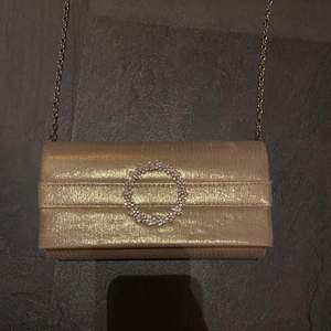En roseguld/glitter väska, med en fin detalj av stenar på framsidan. Långt silverkejda som band, bandet är utbytbart. Magnetknäppe. Endast använd ett fåtal gånger så är i nyskick.