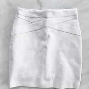 """Kritvit kjol,tjock kvalitet. Strl S, från BikBok.  dragkedja bak.Något stretchig. Längd 40cm.""""innerkjol"""" (ett extra lager tyg på insidan).  Tvätt 40c. 97% polyester, 3% Elastan. sparsamt använd,liten fläck på baksidan (se sista bild).annars i fint skick!"""