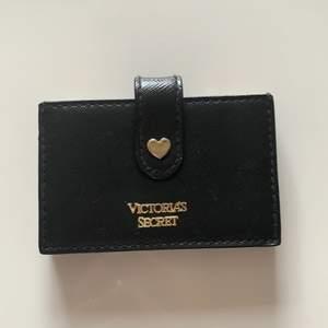 Svart korthållare från Victorias Secret med färgglada kanter. Man stänger den med hjälp av en knapp på framsidan. Får plats med flera kort i samma fack. Använd men är i väldigt bra skick!! Köparen står för frakten🌸