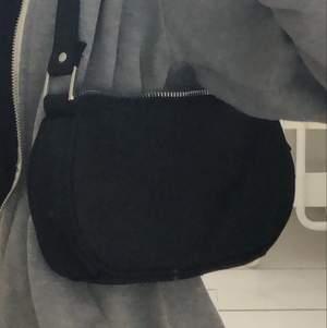 En annan snygg svart matt axelremsväska. Är ca 15X20 cm och har oxå silver detaljer! Har ett fack på baksidan.