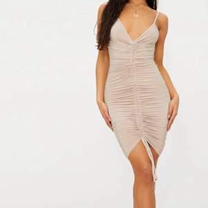 Ryschad midi klänning i en jättefin nude färg. Klänningen har snören ner till, vilket gör att man justera hur lång/kort man vill ha klänningen, samt hur ryschad man vill ha den. Ny och helt oanvänd, säljer då jag inte haft tillfälle att använda den🥺 Ord. Pris £22 (ca 260kr)