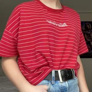 En röd och vit randig t-shirt från H&M divided med broderad text. Tyget är lite tjockare än en vanlig t-shirt. Använd men i bra skick