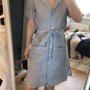 Somrig Blåvitrandig skjortklänning från Nelly med knappar framtill samt knytband i midjan. Aldrig använd då den är inte riktigt min stil.