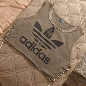En unik Adidas topp som om omsydd från en Adidas sweatshirt. Snygg snörning på sidorna. Lite stor i storlek för mig som har S så skulle säga mer en S/M eller M i storlek om du vill ha den lite mer tajt.