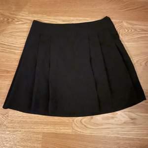 En svart veckad kjol för från New Look, storlek 158 (13år).